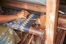 to Jpeg 40K 9809O29 A three colour ikat being woven on a loom in the weaving mill at Innbawkon (Inpawkhon) on Lake Inle, Shan State. Note the tensioning 'bow' fixed across the width (weft) of the woven fabric to keep the tension and width constant.