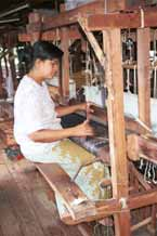 to Jpeg 46K 980930E A three colour ikat being woven on a loom in the weaving mill at Innbawkon (Inpawkhon) on Lake Inle, Shan State. Note the weaver pulling on a cord to activate the 'flying shuttle' which has been added to the traditional Burmese frame loom to speed up the weaving process.