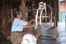 31K Jpeg 9809P04E Intha woman with skeins of silk threads in her lap as she works on the early preparation stages of the threads in the ikat process at a weaving mill at Innbawkon (Inpawkhon) on Lake Inle, Shan State.