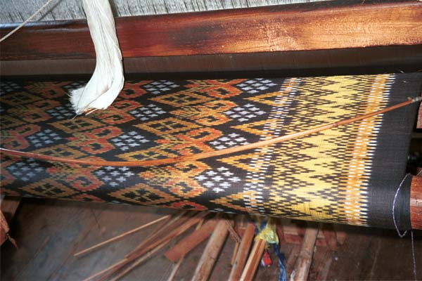 Jpeg K 48K 9809P08 Four colour silk ikat on the loom at a weaving mill at Innbawkon (Inpawkhon) on Lake Inle, Shan State. Note the 'bow' across the width of the weft to keep the width and tension constant.