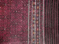 to Jpeg 54K Khumi woman's tubeskirt -detail showing the black warp and red, white and black supplementary weft patterning