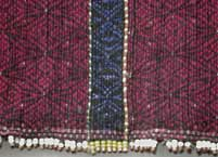 to Jpeg 51K Khumi woman's tubeskirt - detail showing the black warp and red (and light blue) supplementary weft patterning