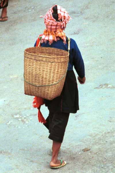 Jpeg 23K 9809J07 Pa'O woman at Kalaw Market, Shan State showing her short jacket over her lose blouse with coloured stitch detail down the back seam. The blouse is worn over a calf length plain longyiNote her woven (from the market) head scarf and Shan bag over her shoulder. Baskets similar to the one on her back were being sold by a Pa'O woman who had carried them into the market balanced on her head.