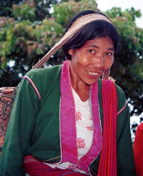 74K Jpeg Silver Palaung woman carrying the weight of a heavy basket on her head in the hills near to Kalaw. It is interesting to note that she has used a deep pink satin brocade for the wide edging around the front and neck of her blouse.