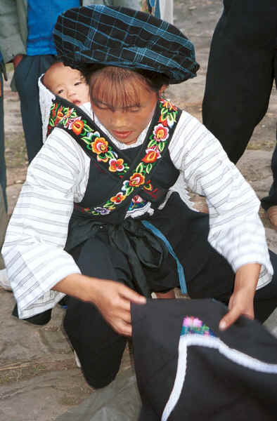 Bouyei mother with her baby on her back spreading out an apron for sale - Bi Ke village, Mi Gu township, Zhenfeng county, Guizhou province 0010s22.jpg