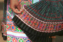 Jpeg 53K Examining a batik skirt the top part of which is in the Clean Water Miao style but has added strip of embroidery rather like the Red Hat Miao - Da Shu Jia village, Xin Zhou township, Longlin county, Guangxi province 0010i35.jpg