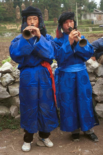 Jpeg 56K  0110D31 Two trumpeters as part of our welcome to Gan He village, Ya Rong township, Huishui county, Guizhou province, south-west China. The people living in this village are known as Qing Miao. There has been much intermarriage between Miao and Bouyei which is evident from the costume of the women.