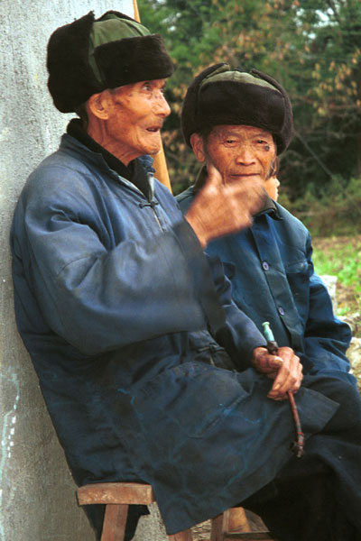 Jpeg 56K  0110D32 Two old men watching our welcome to Gan He village, Ya Rong township, Huishui county, Guizhou province, south-west China. The people living in this village are known as Qing Miao.