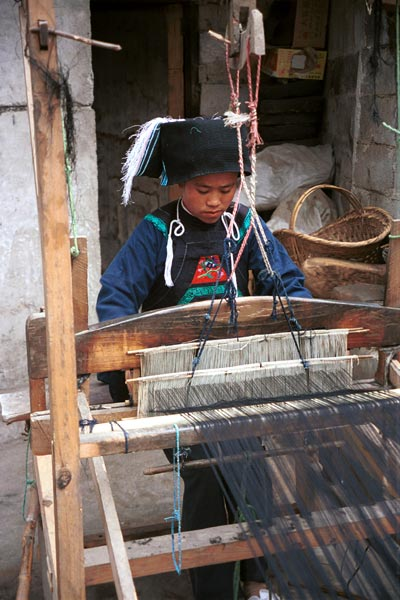 Jpeg 55K  0110E07   Woman weaving an indigo plaid fabric on an upright heddle loom in Gan He village, Ya Rong township, Huishui county, Guizhou province, south-west China. The people living in this village are known as Qing Miao. There has been considerable intermarriage between Miao and Bouyei and the costume is very mixed.