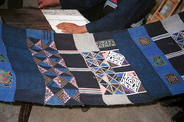 Jpeg 57K  0110E22 A length of pieced fabric ready to be made up into a skirt. Note the wax resist in two shades of indigo, embroidered work and applied plaid triangles of cloth, Gan He village, Ya Rong township, Huishui county, Guizhou province. This is a Qing Miao (or Bouyei/Miao as there has been much intermarriage and the costume is very mixed).
