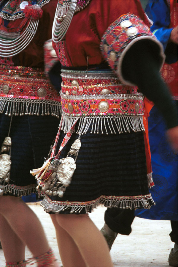 Jpeg 143K Close-up of Iron beating Miao women's costume in Gao Zhai village, Bai Jin township, Huishui county, Guizhou province showing the finely woven, striped skirt and the brightly embroidered braids around the waist 0110C20