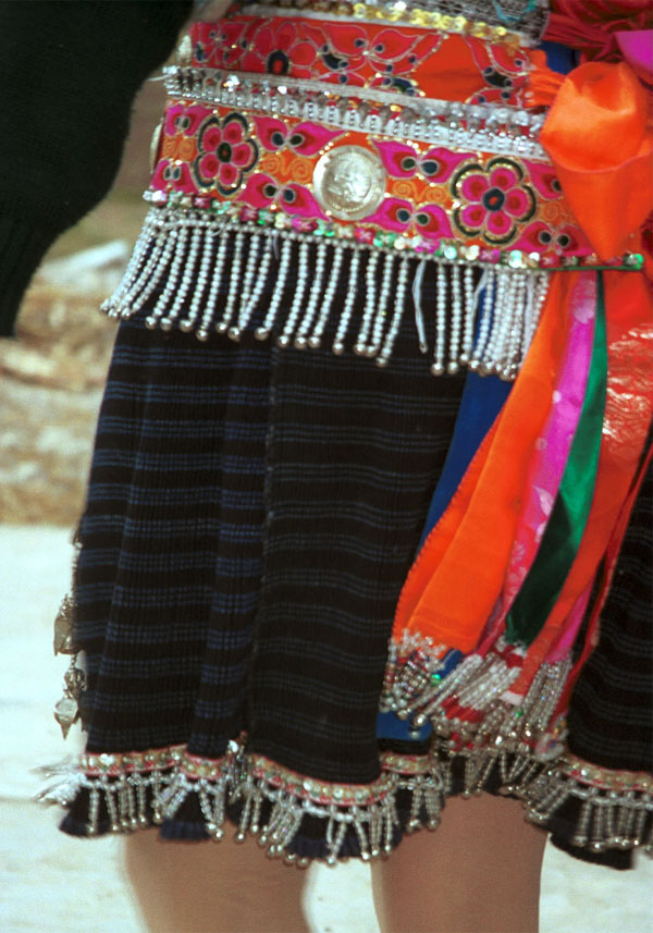Jpeg 133K Close-up of Iron beating Miao women's costume in Gao Zhai village, Bai Jin township, Huishui county, Guizhou province showing the finely woven, striped skirt and the brightly embroidered braids around the waist 0110C21