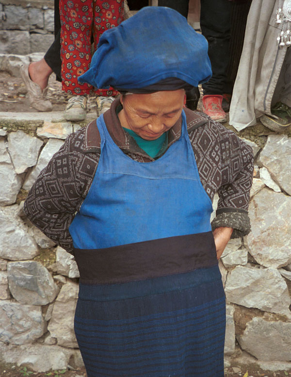 Jpeg 125K Iron beating Miao woman showing me how the finely pleated, woven striped indigo dyed skirt is worn. I have just bought this skirt from her. Her husband had sent her into her house to fetch me a finer one when I had found some mildew on one which she had out for sale. Gao Zhai village, Bai Jin township, Huishui county, Guizhou province 0110D09