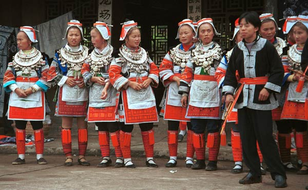 Jpeg 57K 0111G09 Gejia dance troupe performing in Ma Tang village, Kaili City, Guizhou province in November 2001. The apparently wax resist fabric in their costume - at least the headdress, apron and sleeves of the blouse - are now generally made from commercially printed fabric which imitates the Gejia traditional wax resist designs.