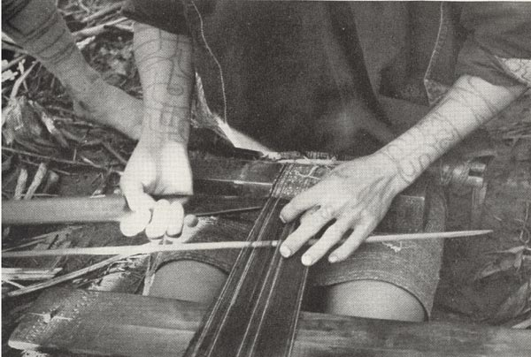 to Jpeg 52K A close up of a Ba-sa-dung woman weaving one of the narrow bands which will be sewn together to make her short tubeskirt.  It is amazing that the very complex designs which are created by these Li women are achieved on such simple looms. The photo comes from the article in the September 1938 National Geographic by Leonard Clark telling of his 5-week trek into the interior of Hainan in the summer of 1937.