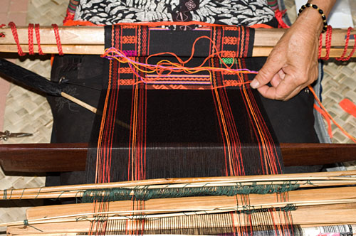 "Weaver Huang Ji Xiang, who is a member of the Qi subgroup of the Li people, making the cloth that is called ""Li brocade"" locally. Weaving proceeds via two separate sheds. A lower shed is opened with the large, dark colored weaving sword, which is twisted to open the shed wider. Black weft is passed through on a spindle and then beaten down with the sword."