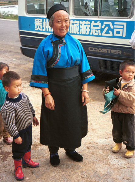 Jpeg 93K Lao Han woman with children who came to see what was happening at the Miao village. She felt that she was not looking smart enough in her apron so took it off to be photographed (see the small boy on the right of the photo holding the apron. Lou Jia Zhuang village, Anshun city, Guizhou province 0110A31