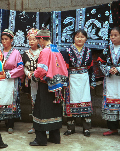 Jpeg 116K Group of Miao women wearing a mixture of clothing including wax resist (batik) and embroidery. The traditional costume has absorbed styles from other Miao as well as other influences. Note the traditional festival hair styles of some of the women. Lou Jia Zhuang village, Anshun city, Guizhou province 0110B12a