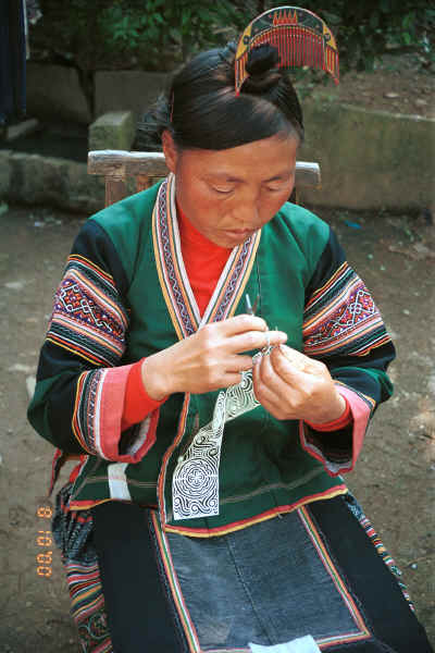 Side Comb Miao married woman finishing off a paper cut-out for embroidery probably for a sleeve insert - Pao Ma Cheng village, Teng Jiao township, Xingren country, Guizhou province 0010n27.jpg