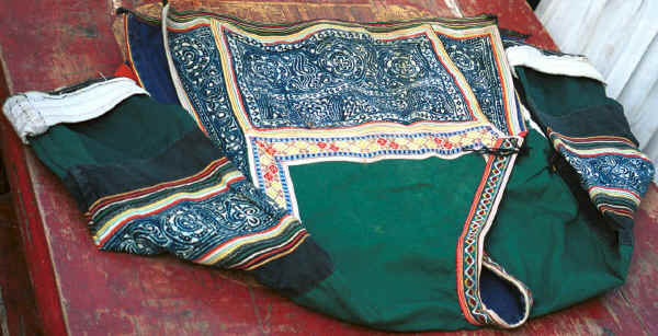 Side Comb Miao girl's jacket.  Note that it is decorated with batik inserts rather than embroidered ones which seem to be the current fashion. Pao Ma Cheng village, Teng Jiao township, Xingren country, Guizhou province. 0010o14.jpg