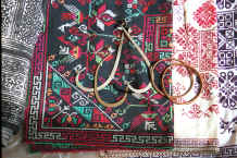 Jpeg 59K Ear rings, bracelets lying on embroidery (possibly for baby carrier pieces) and, to the left, a batik skirt length - Sha Jiao village, Wan Teng township, Xingyi metropolitan area, Guizhou province 0010m15.jpg