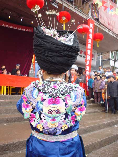 Jpeg 48K Back view of a Miao girl at a festival in a village in Songtao Miao Autonomous County, Tongren Prefecture, eastern Guizhou Province. Note the silver decorations peeping out of the headdress and the bold embroidery collar covering the back of the blouse.