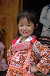 to Jpeg 59K Young Long Horned Miao girl showing off her beautifully embroidered festival costume.