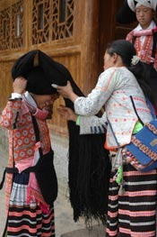 to Jpeg 61K Dressing the hair of a Long Horned Miao girl in festival dress by winding the girl's own hair, wool and perhaps inherited hair around the wooden 'horn'.