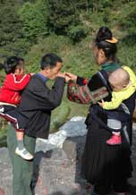 to 72K Jpg image Tony's aunt, wearing festival clothes, offering rice wine to his elder sister's father-in law