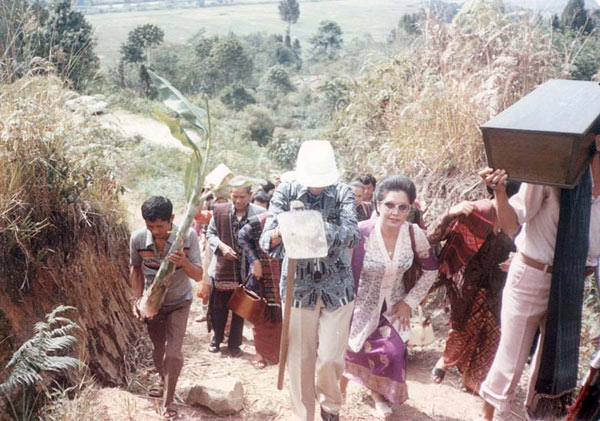 The Tobing family members accompanying the casket of Nai Horja's bones as they are carried up the hill for reburial. Various of her descendants take it in turn to carry the casket. Note how several are wearing traditional ulos.