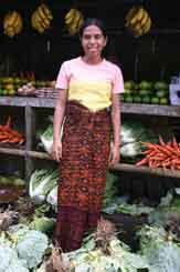 to 53K Jpeg 0161 Roadside fruitseller outside Maumere, Flores (2004). Her sarong reflects the patola influence. (Patola - a double ikat textile originally woven in southern India and traded into Indonesia.)