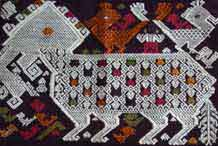 to Jpeg 71K A new (end 20th beginning 21st century) woven fragment of a siho, a mythological animal half-lion, half-elephant unique to the Lao culture and considered to be imbued with special powers shown with an ancestor figure riding on his back between two birds.