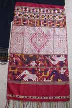 to Silk supplementary weft end of a pha biang showing siho, mythological animals half-lion, half-elephant, unique to the Lao culture, with spirit figures on their backs walking amongst other figures including nak