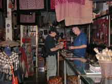 to Jpeg 57K  Bucklee Bell with a customer in his side of the gallery 'Kesorn Arts' which he runs with his wife Kesorn Bell in Chiang Mai 3397