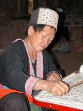 to Jpeg 45K White Hmong woman in Ban Pha-nok-kok village waxing cloth before dyeing.  3441