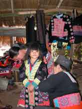 to Young White Hmong girl in Ban Pha-nok-kok village being dressing in traditional festival clothing by her mother and grandmother