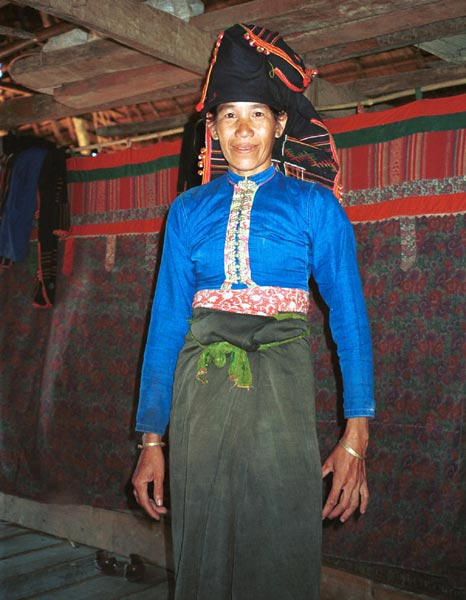 9510D24 Jpeg 55K Black Thai lady showing how her head cloth is worn standing in her house against curtains shielding off the sleeping areas from view and with hand woven cloth pieced into the heading area of the curtains. Dien Bien Phu, Lai Chau Province, October 1995.