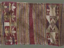 "to Jpeg 59K From Xam Tai, detail of an unusual mosquito net border (now in the collection of Pamela Cross) which is a lovely shade of brown, with accents of purple, gold and yellow. It is unusual because of the design motifs: elongated, stylized star motifs with arrows; also present in a few places are stylized animal motifs and figures with up-raised hands. One end is a dark red (as shown in the detail above) rather than brown. It is all handspun cotton (or perhaps fine hemp?) with cotton and some silk supplementary weft. Condition is very good, tho there are soiled areas throughout. Size: 274"" (22'-10"") x 9.5"""