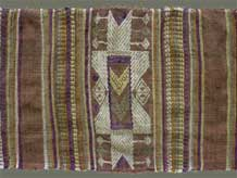 "to Jpeg 63K From Xam Tai, detail of an unusual mosquito net border (now in the collection of Pamela Cross) which is a lovely shade of brown, with accents of purple, gold and yellow. It is unusual because of the design motifs: elongated, stylized star motifs with arrows; also present in a few places are stylized animal motifs and figures with up-raised hands. One end is a dark red rather than brown. It is all handspun cotton (or perhaps fine hemp?) with cotton and some silk supplementary weft. Condition is very good, tho there are soiled areas throughout. Size: 274"" (22'-10"") x 9.5"""
