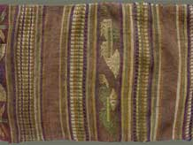 "Jpeg 58K From Xam Tai, detail of an unusual mosquito net border (now in the collection of Pamela Cross) which is a lovely shade of brown, with accents of purple, gold and yellow. It is unusual because of the design motifs: elongated, stylized star motifs with arrows; also present in a few places are stylized animal motifs and figures with up-raised hands. One end is a dark red rather than brown. It is all handspun cotton (or perhaps fine hemp?) with cotton and some silk supplementary weft. Condition is very good, tho there are soiled areas throughout. Size: 274"" (22'-10"") x 9.5"""