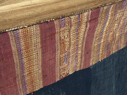 "Jpeg 71K Detail of supplementary weft top band of a Tai Daeng Mosquito Net (pha mung) from Xam Tai in northeast Laos. Approximately: 61"" x 65"" on the sides and 60"" high; hanging pockets extends 4"" from main 'box'. Four panels on each side of handspun, handwoven indigo cotton, with silk and cotton heading border in good condition; top of four panels (one is pieced making three parts) gold-colored handspun, handwoven cotton. One side (side 'd') has a panel replaced, or of darker color indigo. Several patches and some holes, although none are larger than 1"". A few patches of supplementary warp scraps. All handstitched. Early 20th century."