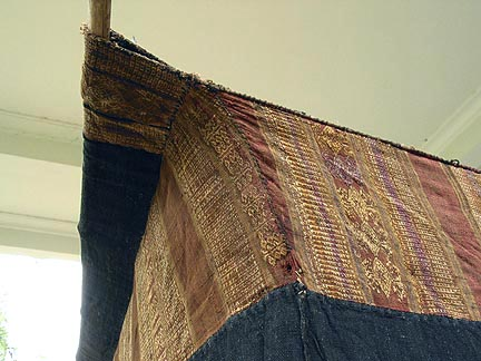 "Jpeg 52K Top corrner hanging detail of Tai Daeng Mosquito Net (pha mung) from Xam Tai in northeast Laos. Approximately: 61"" x 65"" on the sides and 60"" high; hanging pockets extends 4"" from main 'box'. Four panels on each side of handspun, handwoven indigo cotton, with silk and cotton heading border in good condition; top of four panels (one is pieced making three parts) gold-colored handspun, handwoven cotton. One side (side 'd') has a panel replaced, or of darker color indigo. Several patches and some holes, although none are larger than 1"". A few patches of supplementary warp scraps. All handstitched. Early 20th century."