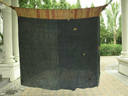 "Jpeg 50K Tai Daeng Mosquito Net (pha mung) from Xam Tai in northeast Laos. Approximately: 61"" x 65"" on the sides and 60"" high; hanging pockets extends 4"" from main 'box'. Four panels on each side of handspun, handwoven indigo cotton, with silk and cotton heading border in good condition; top of four panels (one is pieced making three parts) gold-colored handspun, handwoven cotton. One side (side 'd') has a panel replaced, or of darker color indigo. Several patches and some holes, although none are larger than 1"". A few patches of supplementary warp scraps. All handstitched. Early 20th century."