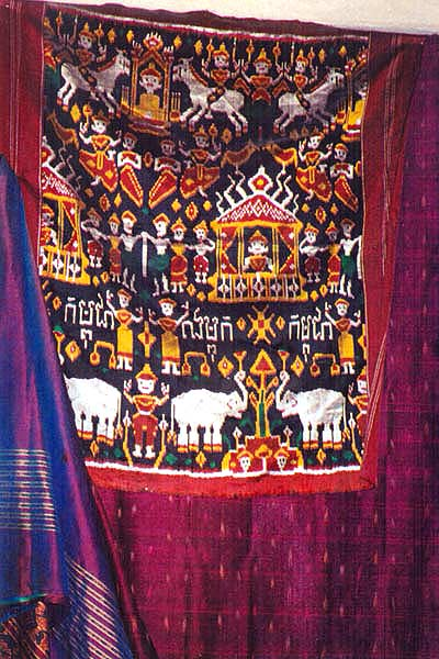 "ss11 Jpeg 56K At my sister's - a pidam with ""kampuchea"" written on it. Under it, a Burmese sarong, on either side, new Khmer silk ikat."