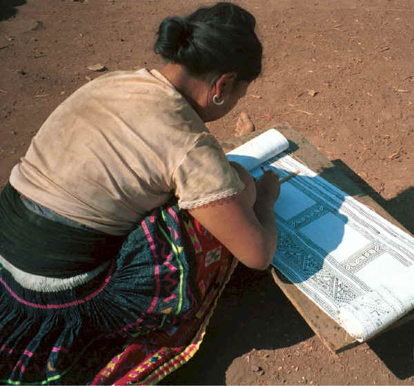 Blue Hmong woman applying wax to a piece of cotton fabric for a skirt (before dyeing with indigo) 8812N30A