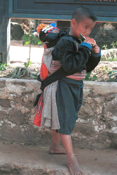 Blue Hmong boy carrying a baby in a baby-carrier on his back in a village on Doi Suthep 8812l01.jpg (363840 bytes)