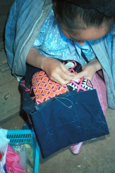 Blue Hmong woman sewing on applique possibly to a young man's jacket 8812l14