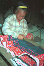 to Jpeg 32K Blue Hmong woman drawing up a skirt into gathers in a village on Doi Chiang Dao on the road from Chiang Mai to Fang 8812n29