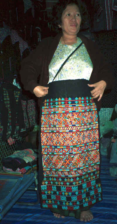 A Yao woman in the Chiang Mai night market holding up a trouser panel for a pair of women's trousers which she had embroidered and which is now in my textile collection 8812m13.jpg