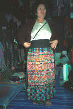 to Jpeg 49K A Yao woman in the Chiang Mai night market holding up a trouser panel for a pair of women's trousers which she had embroidered and which is now in my textile collection 8812m13.jpg